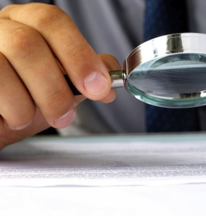 man with magnifying glass looks at paper